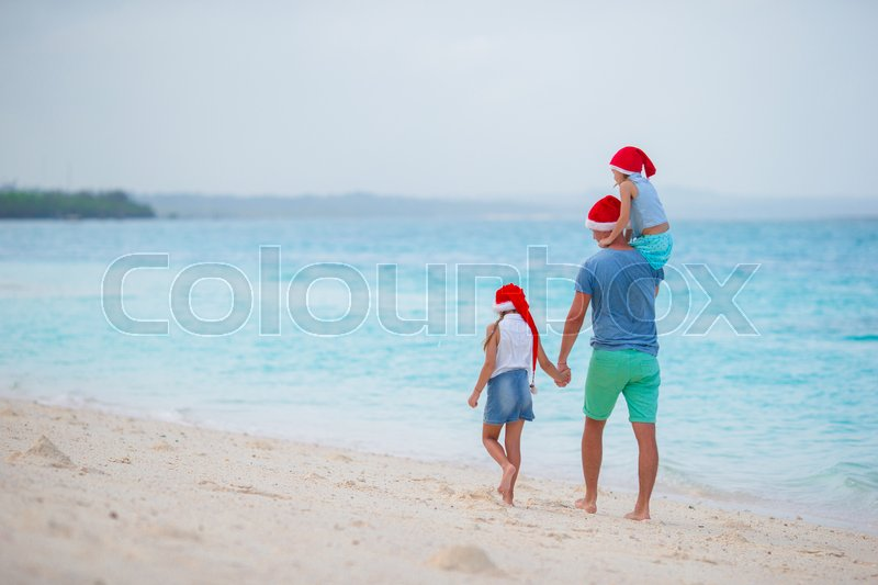 Happy family in Santa Hats on summer vacation. Christmas holidays with young family of four enjoying their sea trip, stock photo