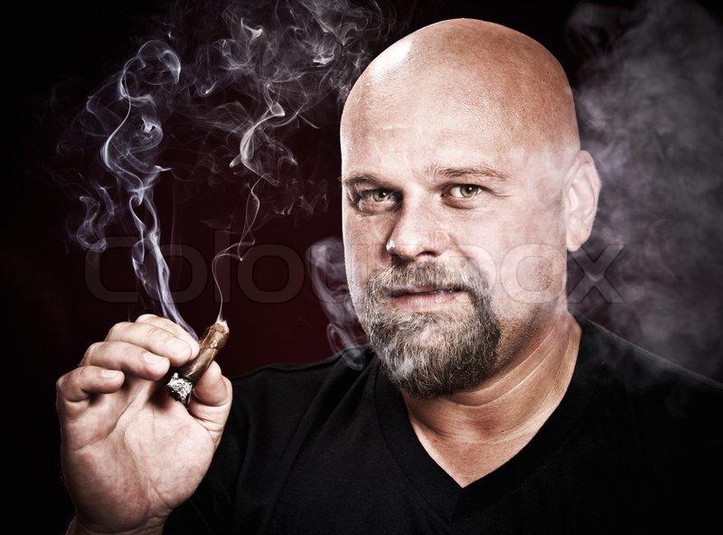 Bald man with a beard smokes a cigar | Stock Photo | Colourbox
