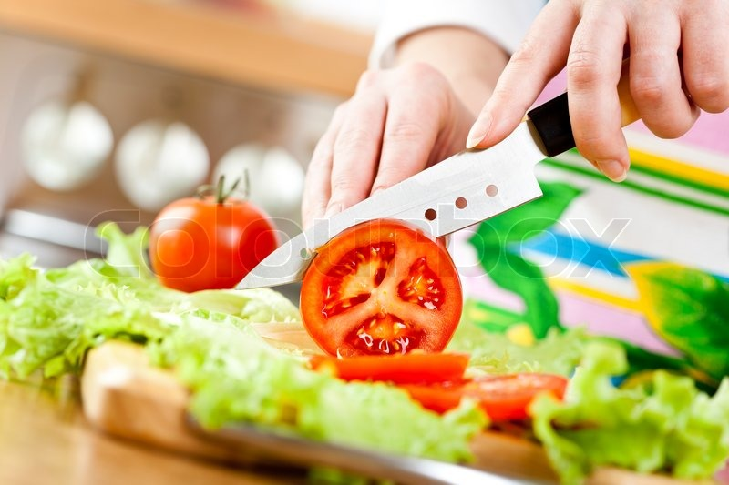 Woman S Hands Cutting Tomato Behind Fresh Vegetables