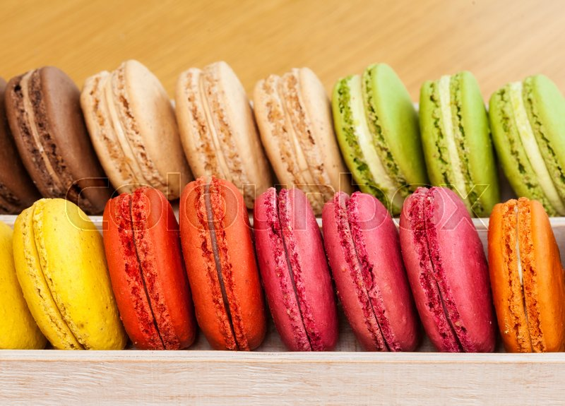 Row of traditional french colorful macarons in a box, close-up, stock photo