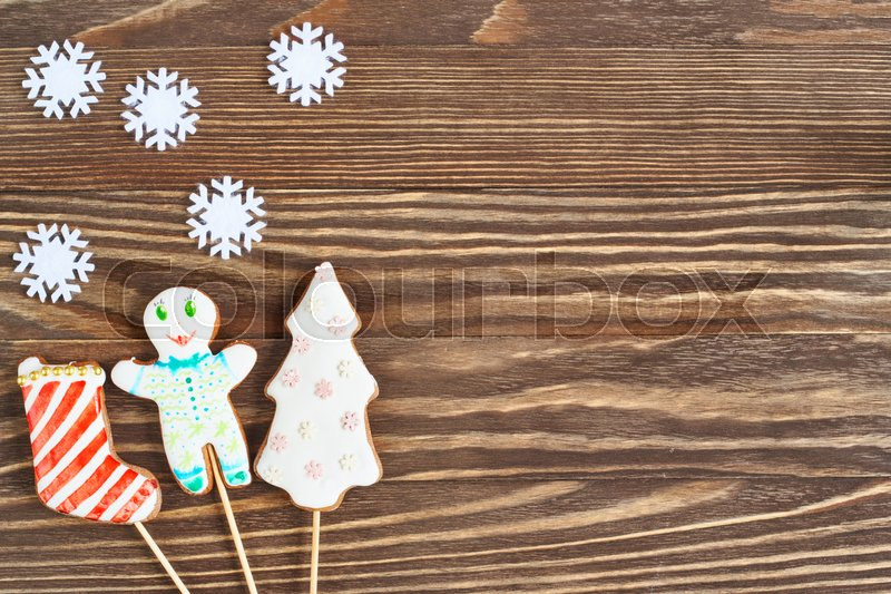 Christmas cookies on stick on wooden background, stock photo