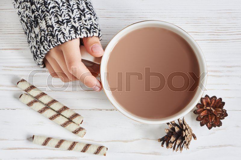 Cocoa cup and woman hand on wooden background, stock photo