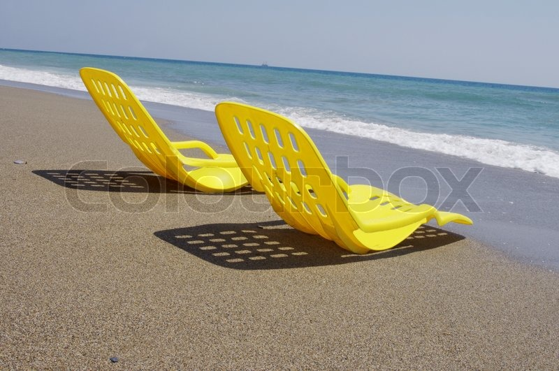 Two Empty Plastic Chairs Stand Under Sunbeams In Day Time On Sand | Stock  Photo | Colourbox