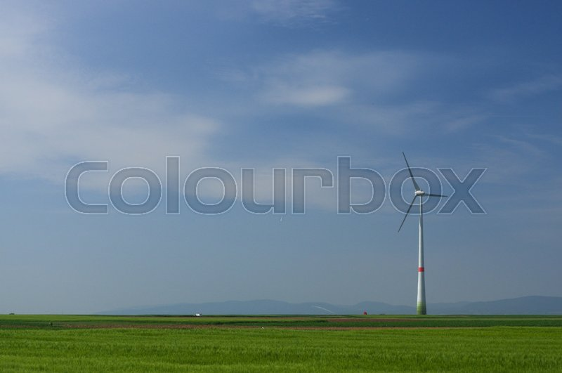 Green meadow with Wind turbines generating electricity, stock photo