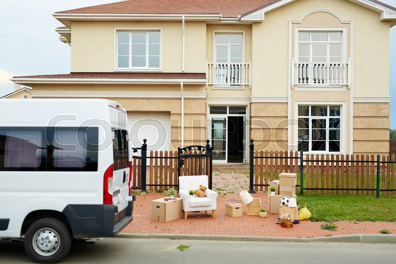 Van and packed things in front of new house outdoors, stock photo