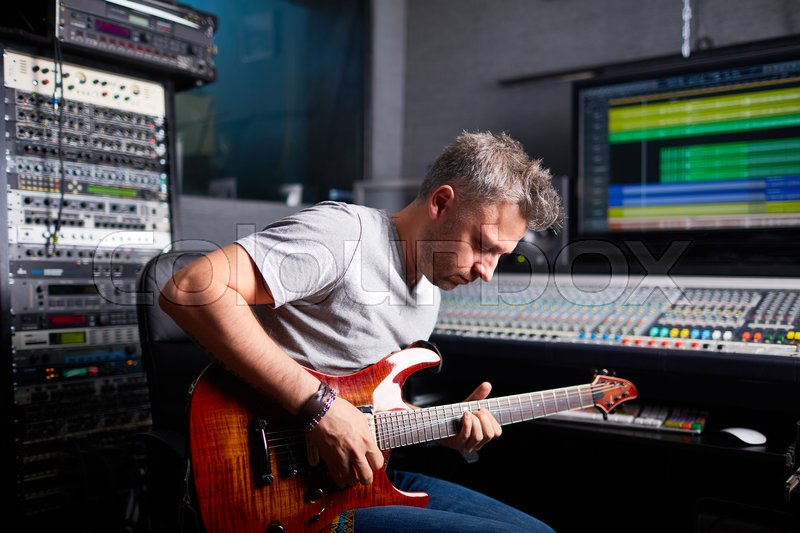 Greyhaired man playing guitar in audio studio, stock photo