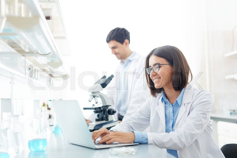 Happy scientist working with electronic data in lab, stock photo
