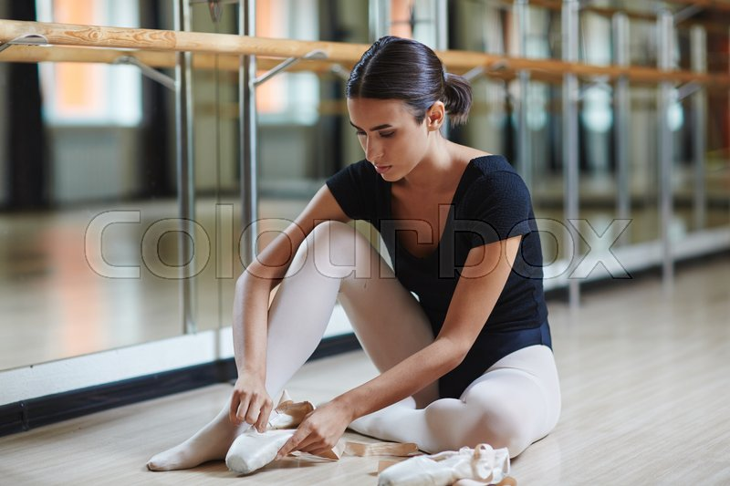 Young ballerina with pointes sitting on the floor, stock photo