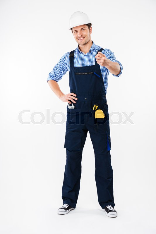 Stock image of 'Cheerful young man builder in hard hat pointing up with both hands'