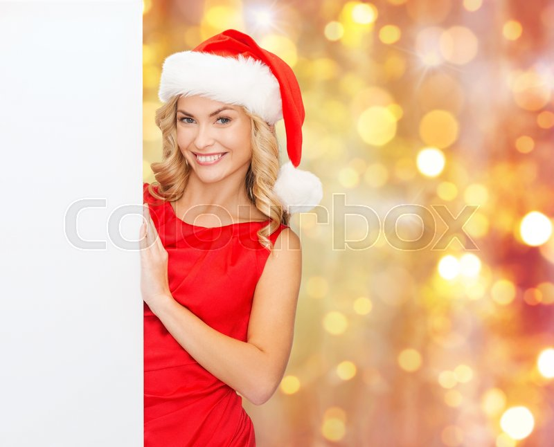 Stock image of 'christmas, people, holidays and advertisement concept - happy woman in santa helper hat with blank white board over lights background'