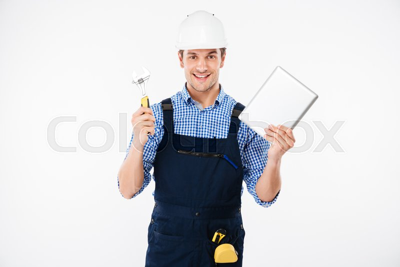 Stock image of 'Happy male builder showing thumb up and holding pc tablet isolated on a white background'