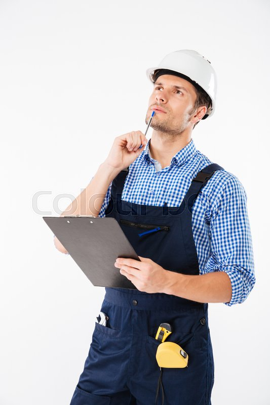 Stock image of 'Pensive young builder in helmet thinking and writing on clipboard isolated on a white background'
