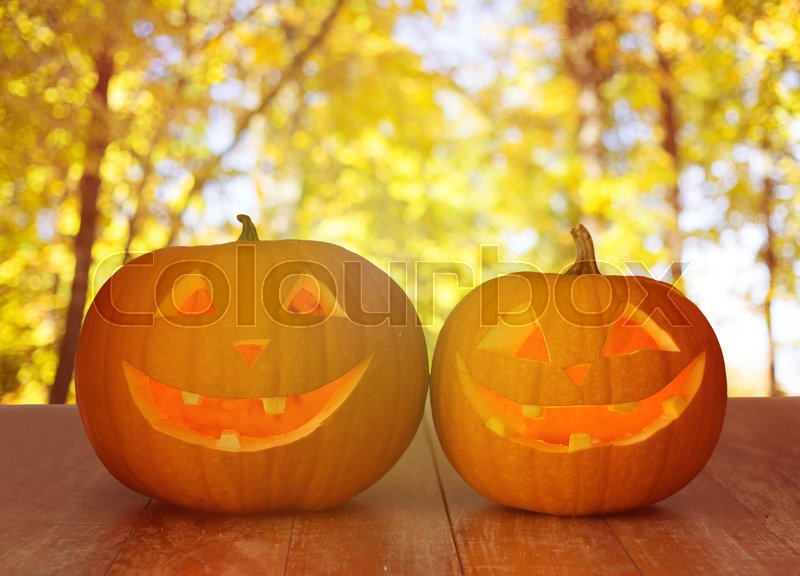 Stock image of 'holidays, halloween and decoration concept - close up of pumpkins on wooden table over natural background'