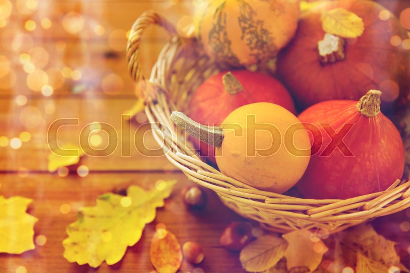 Stock image of 'harvest, season, advertisement and autumn concept - close up of pumpkins in wicker basket with leaves on wooden table at home'