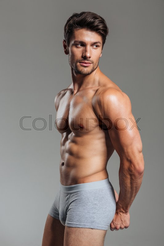 Stock image of 'Sexy young brunette man showing muscles isolated on a gray background'