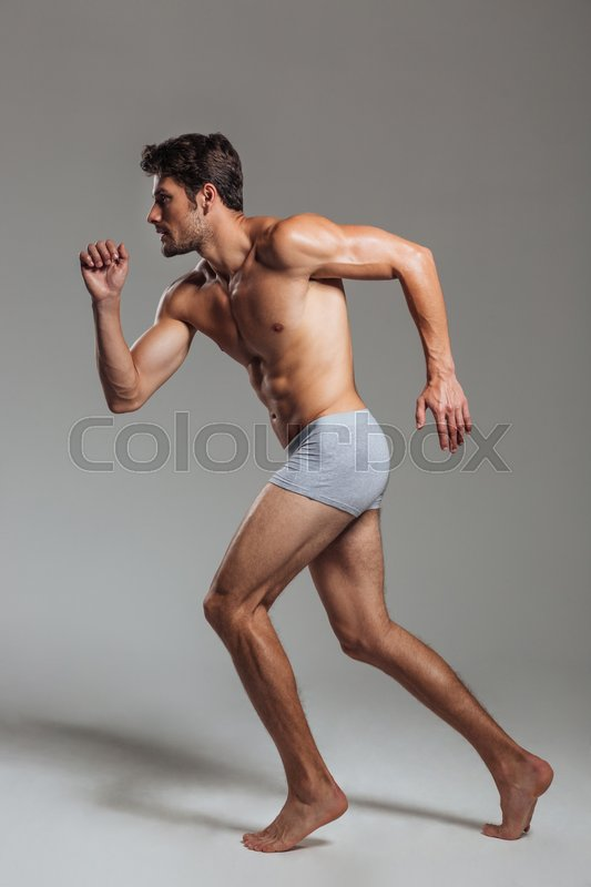 Stock image of 'Full length portrait of a confident young naked athletic man in underwear posing over gray background'