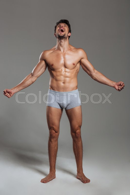 Stock image of 'Full length portrait of a handsome muscular man shouting isolated on a gray background'