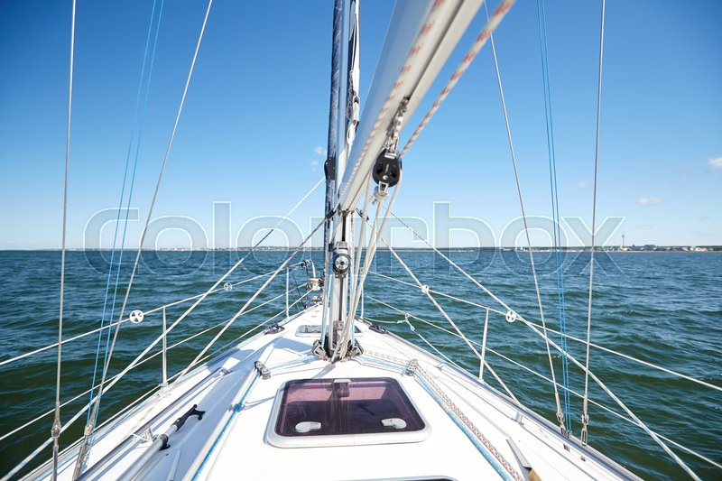 Stock image of 'vacation, travel, cruise and yachting concept - close up of sailboat or sailing yacht deck and sea'