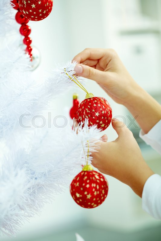 Stock image of 'Female hand hanging red balls on Christmas tree'