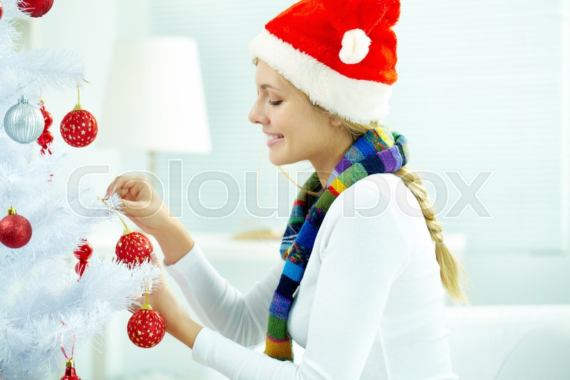 Stock image of 'Young woman decorating Christmas tree'