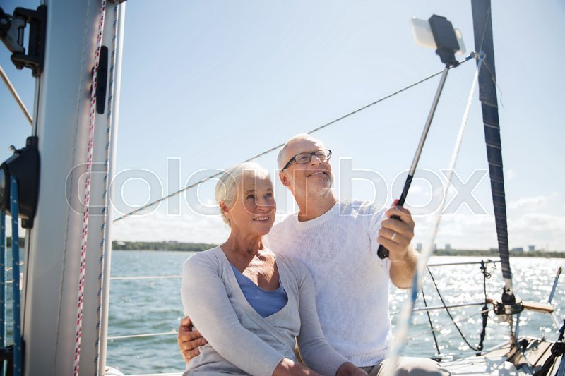 Stock image of 'sailing, age, travel, technology and people concept - happy senior couple with smartphone selfie stick taking picture on sail boat or yacht deck floating in sea'