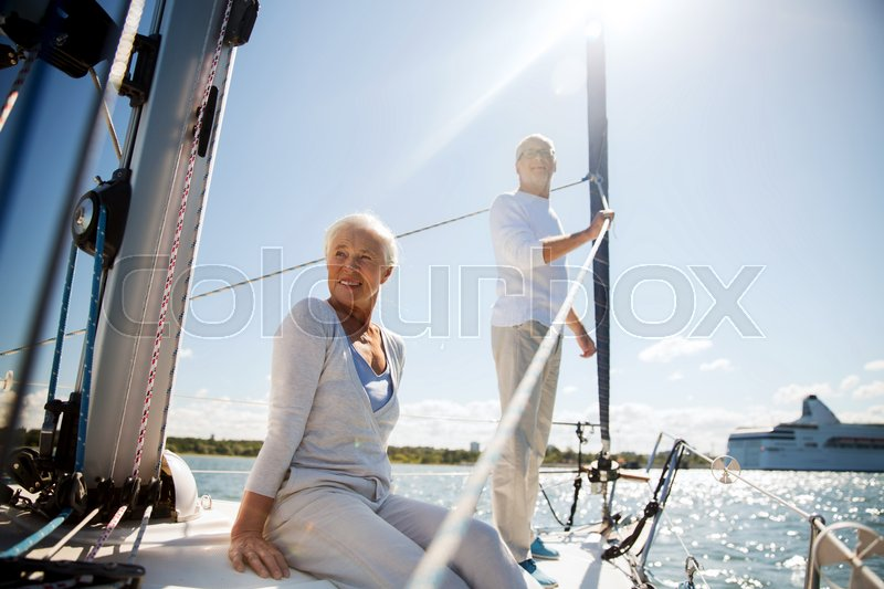 Stock image of 'sailing, age, tourism, travel and people concept - happy senior couple hugging on sail boat or yacht deck floating in sea'