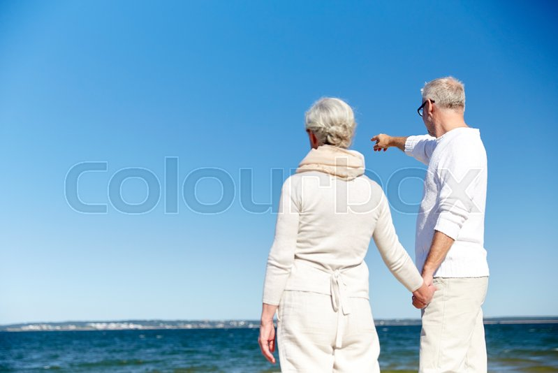 Stock image of 'family, age, travel, tourism and people concept - happy senior couple pointing finger to something over sea'