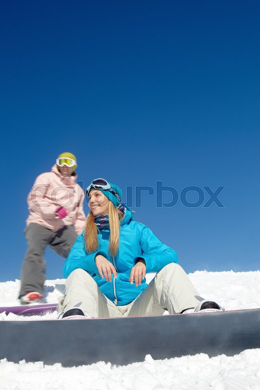 Stock image of 'Snowboarders resting at the top of a mountain'