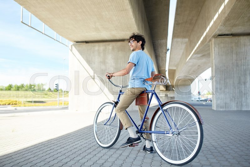 Stock image of 'people, style, leisure and lifestyle - young hipster man riding fixed gear bike on city street'