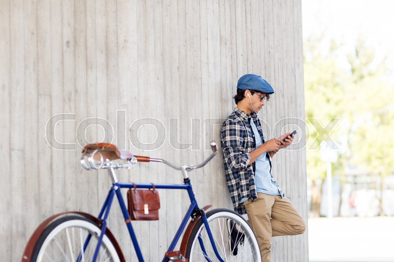 Stock image of 'people, communication, technology and lifestyle - hipster man with smartphone, earphones and fixed gear bike listening to music on city street'