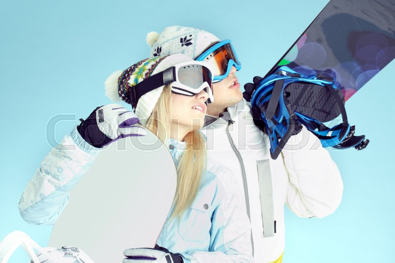 Stock image of 'Young people wearing ski goggles and holding snowboards looking at something'