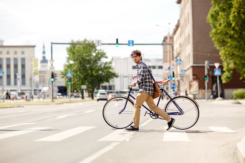 Stock image of 'people, style, city life and lifestyle - young hipster man with shoulder bag and fixed gear bike crossing crosswalk on street'
