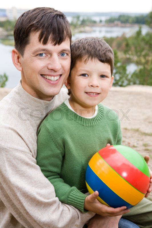 Stock image of 'Portrait of father embracing his son holding ball'
