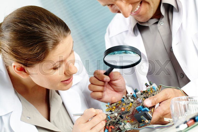 Stock image of 'Serious woman working with circuit board while smiling man examining it with magnifying glass'