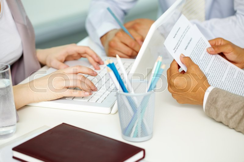 Stock image of 'Close-up of business people's hands working at the table'