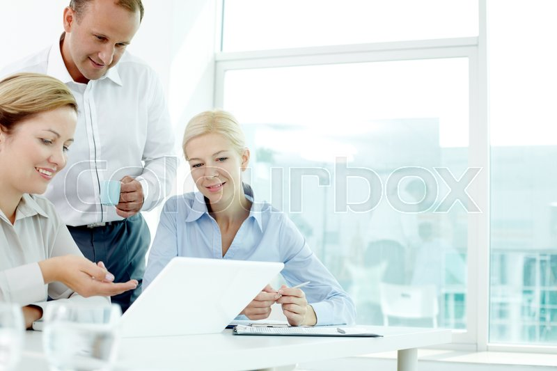 Stock image of 'Businesswoman explaining her presentation on laptop to her two colleagues'