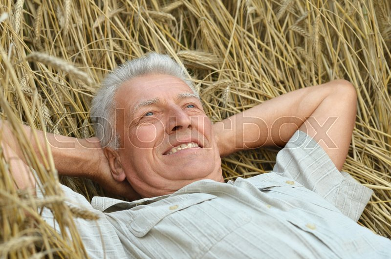 Stock image of 'Portrait of a happy senior man in summer field'