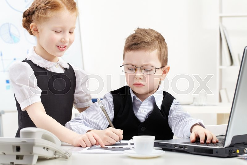Stock image of 'Little boy and girl working together in office'