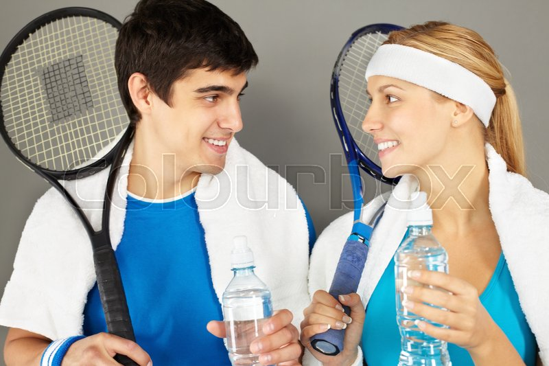 Stock image of 'Young couple with tennis rackets drinking water, looking at each other and smiling'