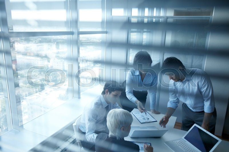 Stock image of 'Four business people working over documents'