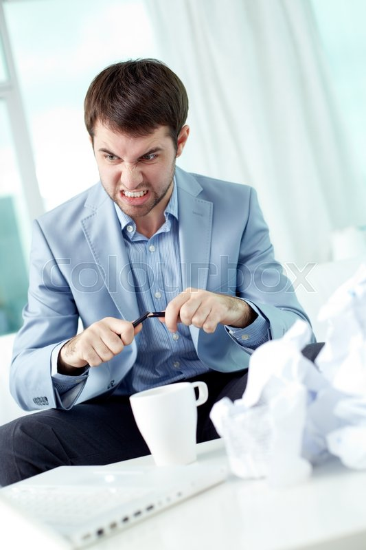 Stock image of 'Angry businessman working with papers at the table'