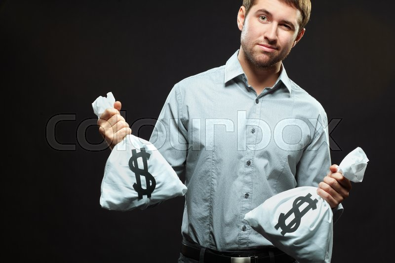 Stock image of 'Young man standing with two money bags and looking at camera'