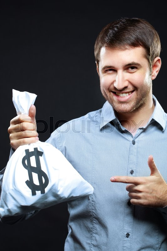 Stock image of 'Happy man pointing at money bag and winking'
