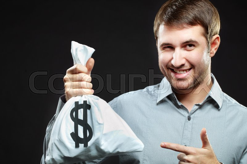 Stock image of 'Smiling man holding money bag and winking'