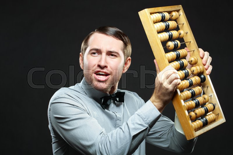 Stock image of 'Aggravated businessman holding an old fashioned abacus on black background'
