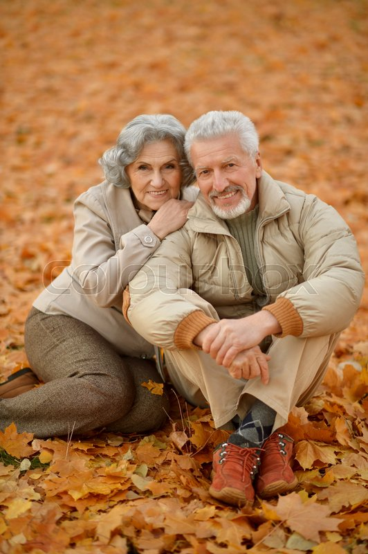 Stock image of 'Portrait of a happy senior couple in autumn park'
