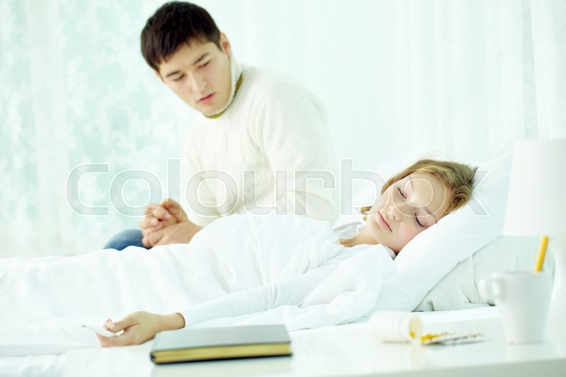 Stock image of 'Man looking anxiously at his wife that fell asleep with fever'