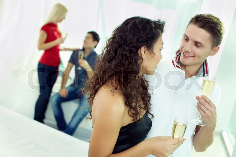 Stock image of 'Young people with champagne flute communicating with each other'