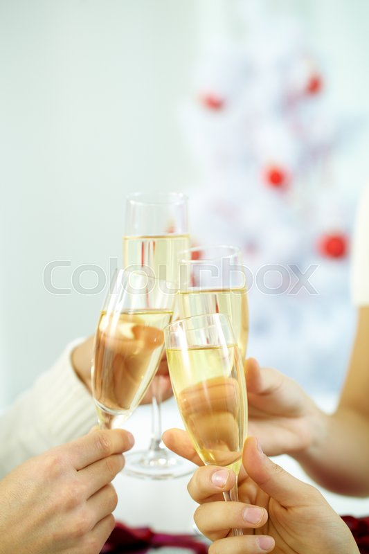 Stock image of 'Close-up of hands clinking champagne glasses'