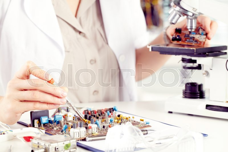 Stock image of 'Close-up of female hands working with transistor'